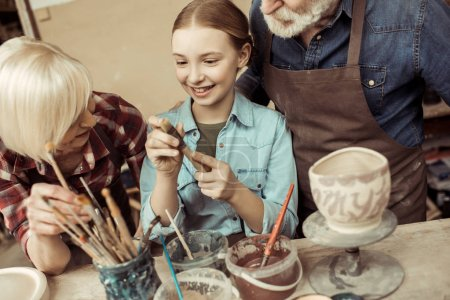 Photo pour Vue de face de fille peinture pot d'argile et grands-parents aider à l'atelier - image libre de droit