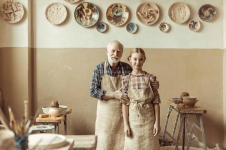 Front view of senior potter with his granddaughter in aprons standing at workshop