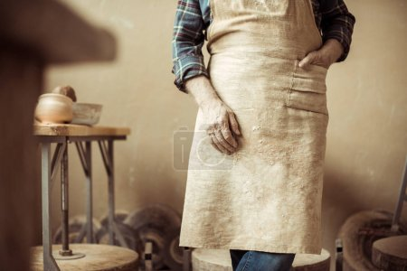 Cropped image of senior potter in apron standing at workshop