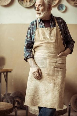 Front view of senior potter in apron standing at workshop