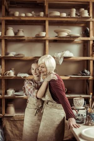 Granddaughter hugging her grandmother while they standing in aprons at workshop
