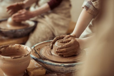 Close up of child hands working on pottery wheel at workshop