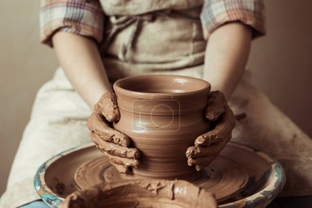 Photo for Close up of child hands working on pottery wheel at workshop - Royalty Free Image