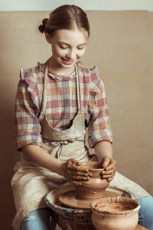 Front view of little girl making pottery on wheel at workshop