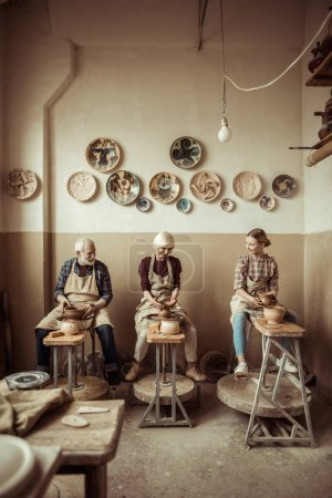 Photo for Grandmother and grandfather with granddaughter making pottery at workshop - Royalty Free Image