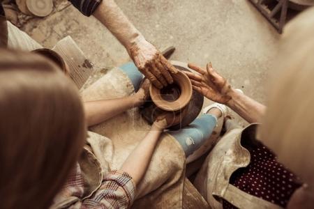 Vista aérea de la niña haciendo cerámica en la rueda con la ayuda de los abuelos en el taller