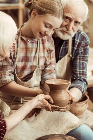 Großmutter und Großvater mit Enkelin beim Töpfern in der Werkstatt