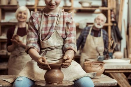 Abuela y abuelo con nieta haciendo cerámica en el taller