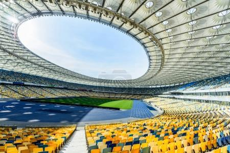 Photo for Rows of yellow and blue stadium seats on soccer field stadium - Royalty Free Image