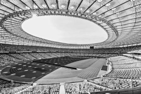 Photo for Rows of yellow and blue stadium seats on soccer field stadium, black and white - Royalty Free Image