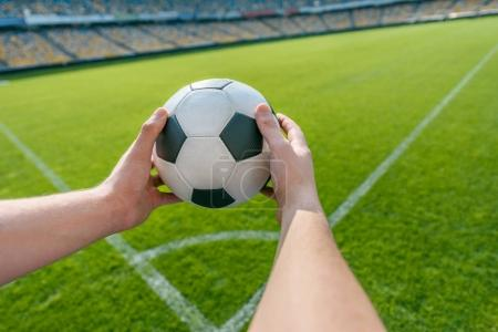Photo for Person holding soccer ball on soccer field stadium - Royalty Free Image