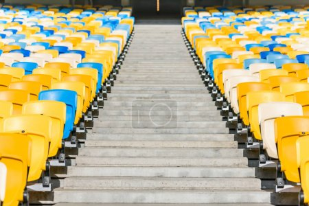 Photo for Rows of yellow and blue stadium seats and stadium stairs - Royalty Free Image