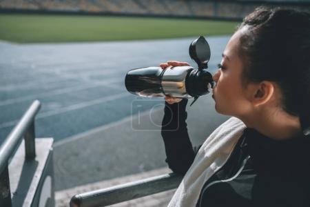asian sportswoman drinking water