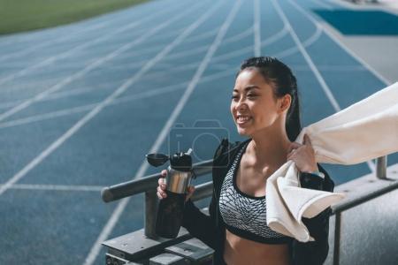 Photo pour Sportive asiatique avec bouteille de sport et serviette sur piste de course sur le stade - image libre de droit