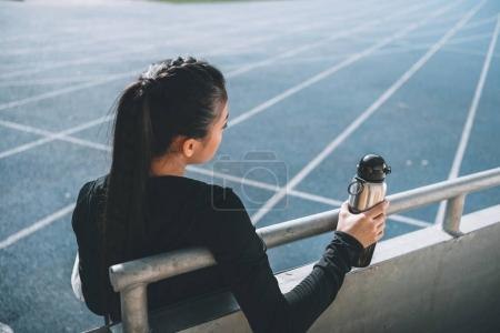 Photo for Asian sportswoman with sport bottle on running track on stadium - Royalty Free Image