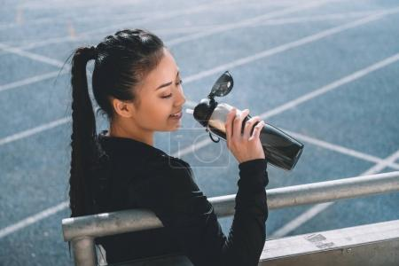 asian sportswoman drinking water