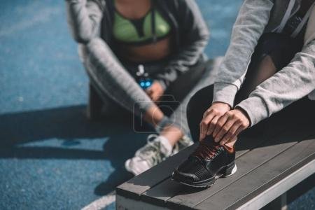 Photo for Two athletic young women in sportswear resting together on stadium - Royalty Free Image