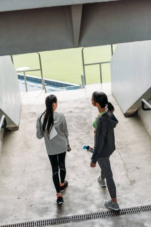 sportswomen at handrail on stadium
