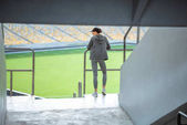 sportswoman at handrail on stadium
