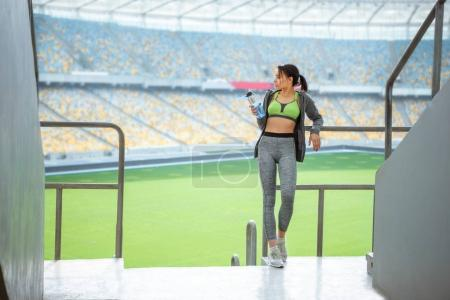 sportswoman at handrail on stadium