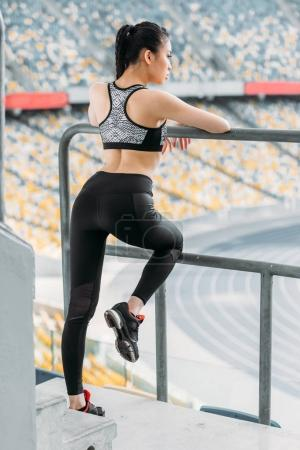 Young sportswoman stretching