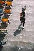 sportswoman running on stadium stairs