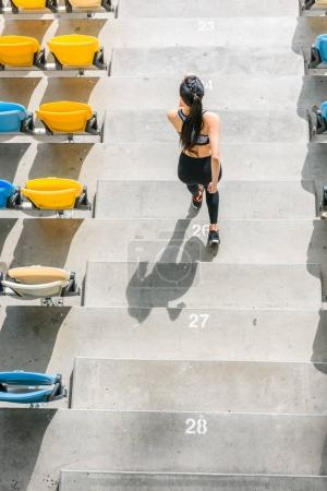 sportswoman running on stadium stairs