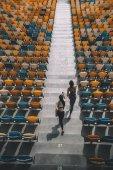 sportswomen running on stadium stairs