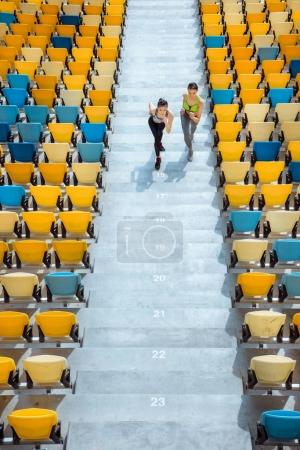 sportswomen running on stadium stairs