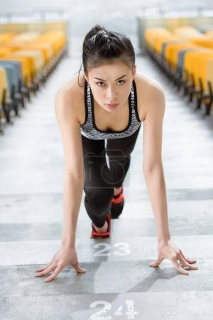 Photo for Young asian sportswoman in starting position on stadium stairs, fitness woman running concept - Royalty Free Image