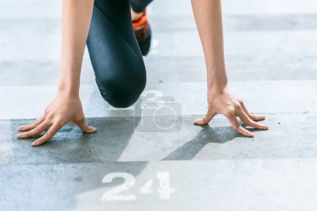 Photo for Partial view of sportswoman in starting position on stadium stairs, fitness woman running concept - Royalty Free Image