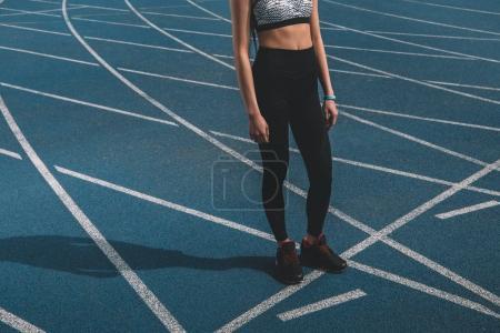 sportswoman standing on running track