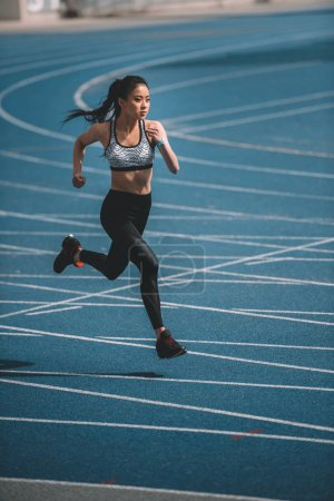 Photo for Athletic young sportswoman sprinting on running track stadium - Royalty Free Image