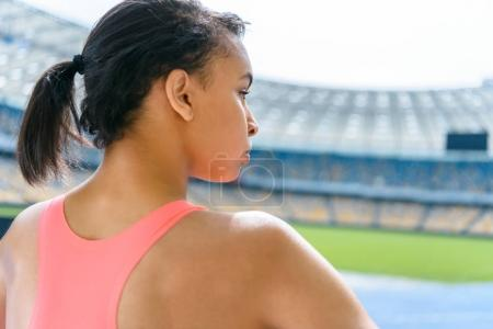 Photo for Young beautiful sportswoman standing on running track stadium and looking away - Royalty Free Image