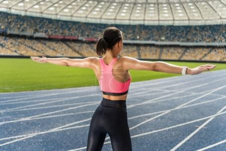 Sportswoman exercising on stadium