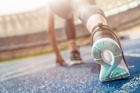 Photo for Close-up partial view of young sportswoman in starting position on running track stadium - Royalty Free Image