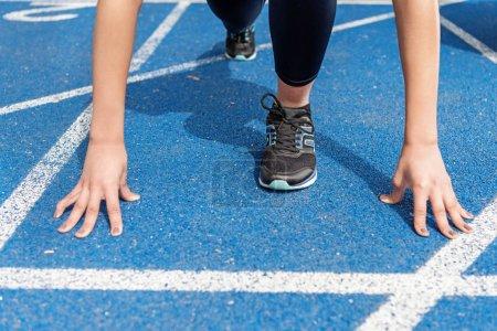 Foto de Vista parcial del primer plano del deportista en línea de salida en la pista de Atletismo estadio - Imagen libre de derechos