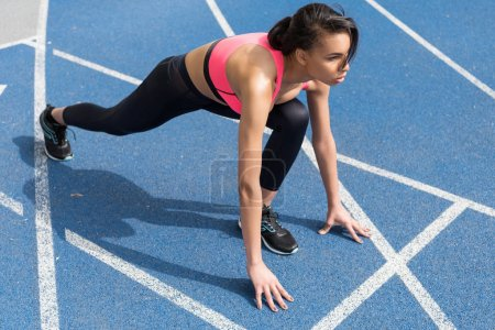 Photo for Concentrated athletic young runner on starting line at running track stadium - Royalty Free Image