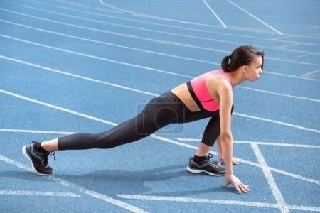 Photo for Side view of athletic young woman in sportswear on starting line ready to run - Royalty Free Image