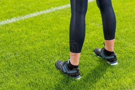 Photo pour Gros plan vue partielle de la sportive debout sur l'herbe du stade de football - image libre de droit