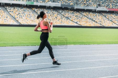 Photo for Side view of athletic young woman in sportswear sprinting on running track stadium - Royalty Free Image