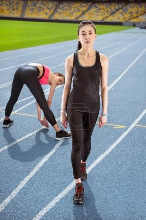 Photo for Athletic young women in sportswear exercising on running track stadium - Royalty Free Image