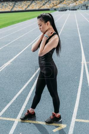 Photo for Young tired asian sportswoman standing on running track stadium and looking down - Royalty Free Image