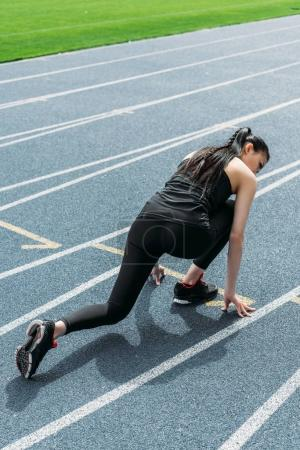 Photo for Back view of young sportswoman in starting position on running track stadium - Royalty Free Image