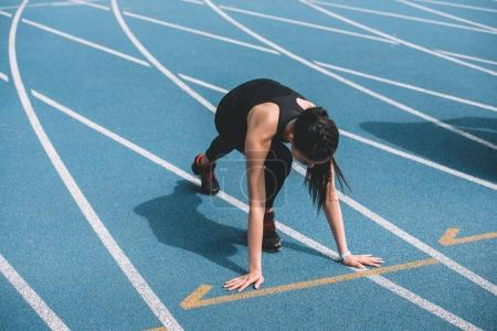 Photo for Concentrated young sportswoman in starting position on running track stadium - Royalty Free Image