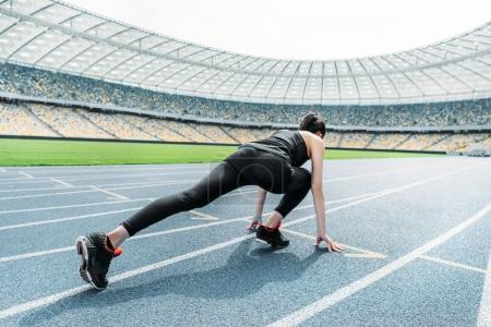 Photo for Young fitness woman in sportswear in starting position on stadium - Royalty Free Image