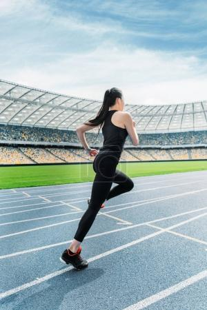 Photo for Young fitness woman in sportswear running on running track stadium - Royalty Free Image