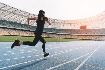 Photo for Athletic young woman in sportswear sprinting on running track stadium at sunset - Royalty Free Image