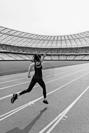 Photo for Back view of young fitness woman in sportswear sprinting on running track stadium, black and white photo - Royalty Free Image