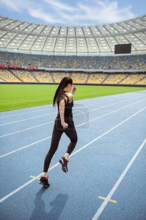 Photo for Back view of young fitness woman in sportswear sprinting on running track stadium - Royalty Free Image